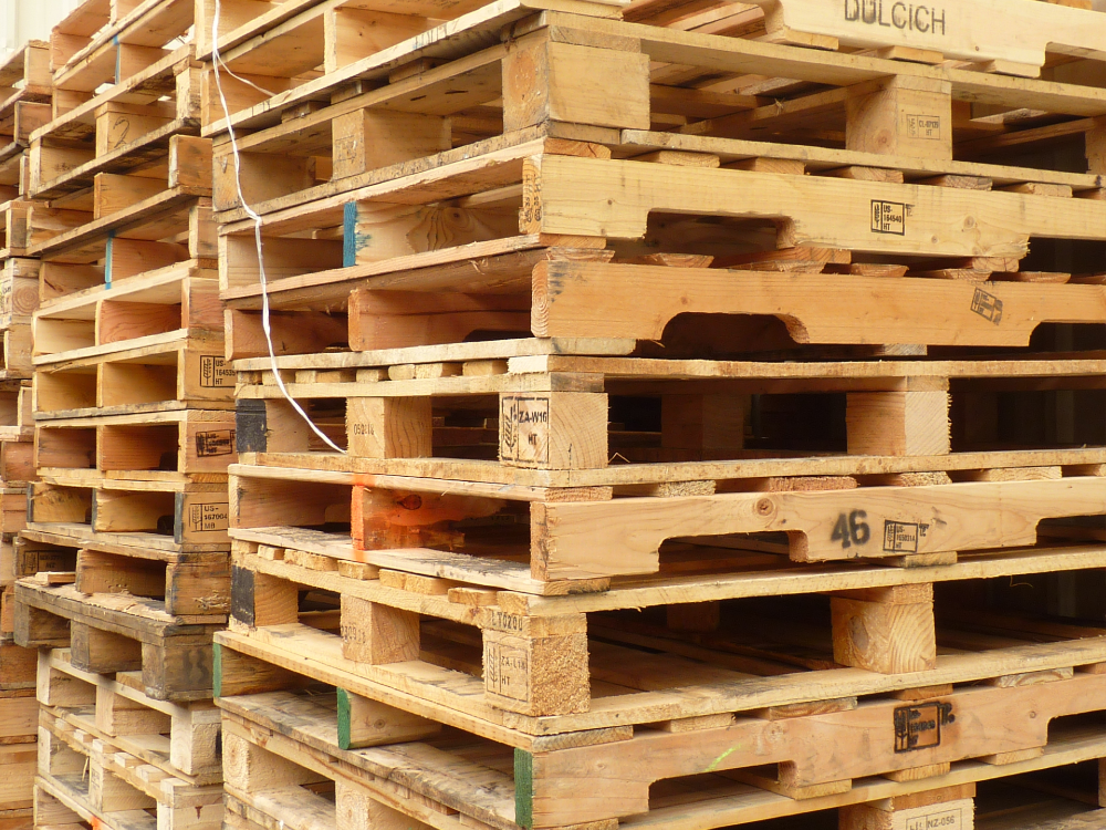 stack of mixed pallets of new and used pallets offered as pallet services.